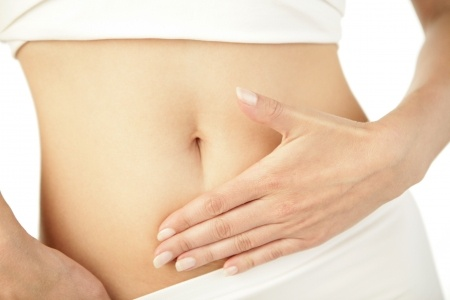 Frau fasst sich an den Bauch